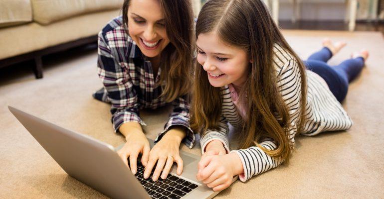 Mère et fille utilisant un ordinateur portable dans le salon
