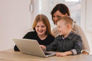 Mère avec des enfants qui jouent sur un ordinateur portable